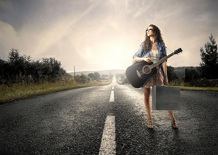 girl on a road with a guitar