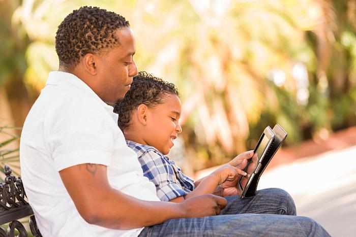 kozzi-5692935-mixed race father and son using touch pad computer tablet-883x588