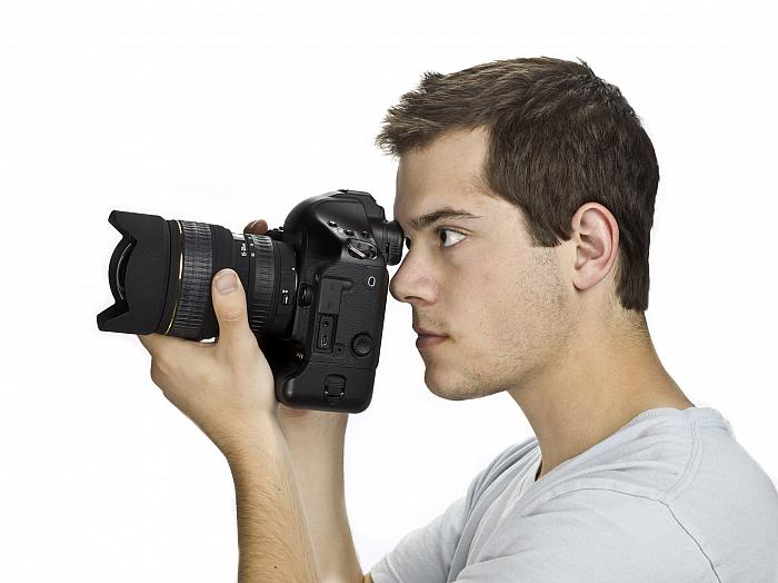 side view of a photgrapher using an SLR camera